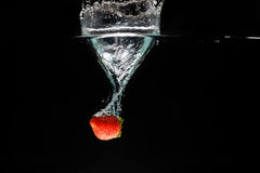 A strawberry splashing into water Royalty Free Stock Image