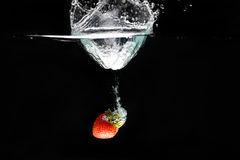 A strawberry splashing into water Stock Photography