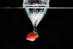 A strawberry splashing into water Royalty Free Stock Photos