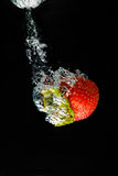A strawberry splashing into water royalty free stock photo