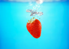Strawberry splashing water Stock Photos