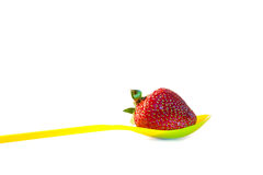 Strawberry in spoon. Strawberry with leaves in a yellow spoon isolated on a white background Royalty Free Stock Images