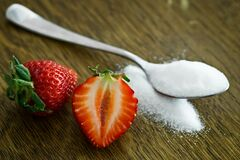 Strawberry Beside Spoon of Sugar Royalty Free Stock Photo