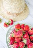 Strawberry and straw hat. Summer still life. Royalty Free Stock Photo