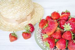 Strawberry and straw hat. Summer still life. Stock Image
