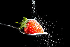 Strawberry and Sugar. Picture of a Strawberry being sprinkled with Sugar royalty free stock images