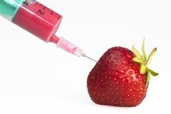 Strawberry with syringe. Toxic or genetically modified strawberry with syringe Stock Photo