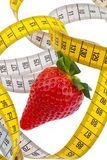 Strawberry and tape measure for a successful diet Stock Photos