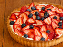 Strawberry tart. A homemade strawberry tart with fresh blueberries, cream cheese filling, and a hand rolled pie crust sits on a wooden table top Stock Photos