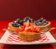 Strawberry tart with blueberry tarts in the background. stock images