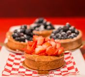Strawberry tart with blueberry tarts in the background. stock image