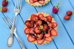 Strawberry tart with mascarpone and licorice syrup served with v. Intage forks on blue table overhead view royalty free stock photo
