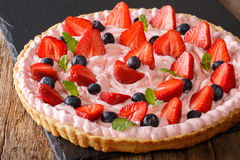 Strawberry tart with pink whipped cream, mint and blueberries. h Royalty Free Stock Image