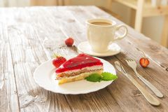 Strawberry tart on plate with coffee on wooden table Royalty Free Stock Image