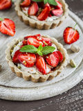 Strawberry tartlet with vanilla cream on a light rustic wooden board. Sweet delicious summer dessert royalty free stock photography