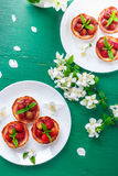 Strawberry tartlet on white plates on green background. Top view. Stock Images