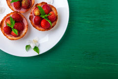 Strawberry tartlet on white plates on green background. Top view. Royalty Free Stock Photo