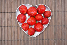 Strawberry. Tasty strawberry on wooden background. White heart. Valentine Royalty Free Stock Images