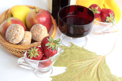 Strawberry. Three berries of strawberry against a glass with wine and baskets with gingerbreads Stock Images