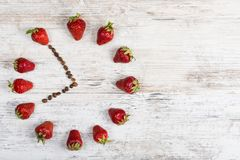 Strawberry clock with arrows from coffee beans, showing the time of seven hours fifty-five minutes or nineteen hours fifty-five mi. Strawberry time is the time royalty free stock images