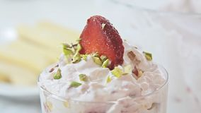 Strawberry tiramisu dessert. With cheese cream in transparent glass on kitchen table video footage filmed in slow motion from low angle closeup stock footage