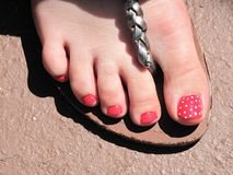 Strawberry toe. Right foot toes painted strawberry pink with white dots in bright high noon sunlight stock photo