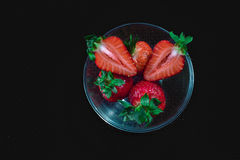 Strawberry. In transparent plate on solid background. Black royalty free stock photography