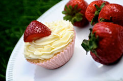 Strawberry and Vanilla Cupcakes on Grass. Strawberry and Vanilla Cream Cupcakes with fresh strawberries on top on a white plate on dark green grass Stock Photo