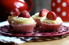 Strawberry and Vanilla Cupcakes in Kitchen. Beautiful creamy strawberry and vanilla cupcakes on a kitchen table with a red spotty mug in the background and fresh Stock Photos