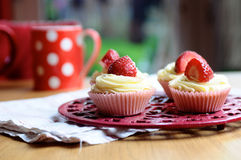 Strawberry and Vanilla Cupcakes on Kitchen Table. Beautiful creamy strawberry and vanilla cupcakes on a kitchen table with a red spotty mug in the background and Stock Images