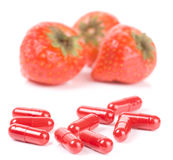 Strawberry vs pills, focus is on capsules Royalty Free Stock Photography