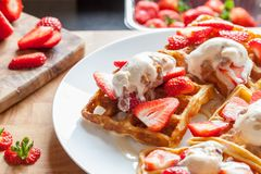 Strawberry waffles. Sweet dessert preparation. Serving with home-made ice cream royalty free stock photo