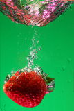 Strawberry in water. A strawberry dropped into water in front of a green background Royalty Free Stock Photo