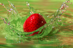 Strawberry on water. Strawberry splashing into green plate with water Royalty Free Stock Photography
