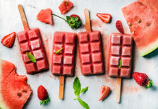 Strawberry watermelon ice cream popsicles with mint over steel tray background. Top view royalty free stock photography