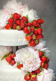 Strawberry wedding cake with floral decorations. Double decker wedding cake made mass of sugar with fresh, red strawberries decorated bright pink flowers Stock Images