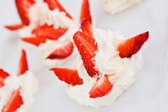 Strawberry with whipped cream. Slices of a strawberry with whipped cream Stock Images