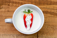 Strawberry with whipped cream into milk. cup with milk and strawberry on wooden background Royalty Free Stock Image