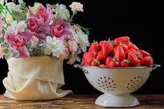 Strawberry in white Bowl with flowers. On dark background. Isolated on black background Royalty Free Stock Images