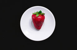 Strawberry. On a white plate , dark background, facture. Natural light royalty free stock image