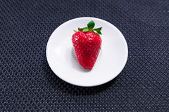 Strawberry on a white plate. On dark background with texture stock illustration
