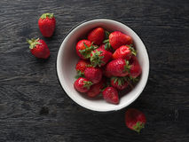 Strawberry in white plate on dark wood Stock Images