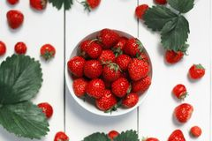 Strawberry on a white wood background. Selective focus on strawberries in the bowl Stock Photography