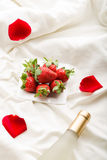 Strawberry, wine and  rose petals Royalty Free Stock Photos