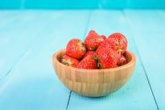 Strawberry Wood Bowl On Blue Background Stock Photo