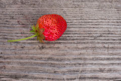 Strawberry on wooden background closeup. Ripe strawberry on wooden background closeup with no leaves Royalty Free Stock Image