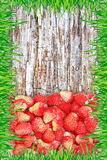 Strawberry on a wooden background with a frame made of grass. Royalty Free Stock Images