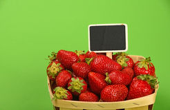 Strawberry in wooden basket with price sign Royalty Free Stock Images
