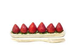 Strawberry in wooden dish and wooden fork on white background Stock Images