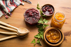 Strawberry and Yellow Cherry Jam on a wooden surface. Stock Photography